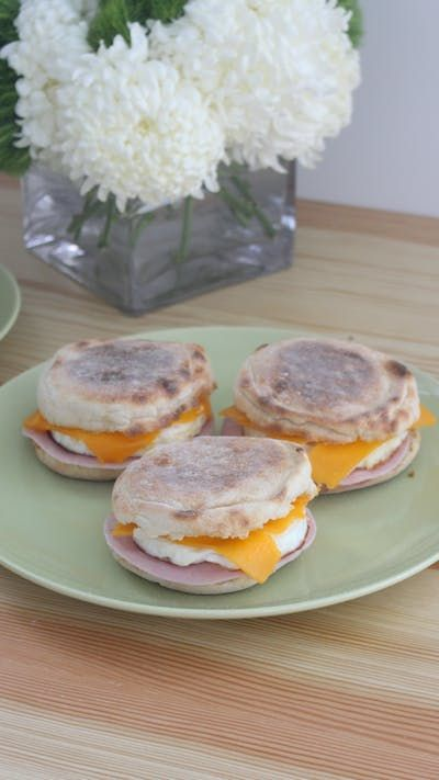 Recipe with video instructions: Save time and money by making your McMuffin fresh at home. Ingredients: 4 eggs, thinly sliced cheddar cheese, 4 English muffins, toasted, butter, 4 slices of ham