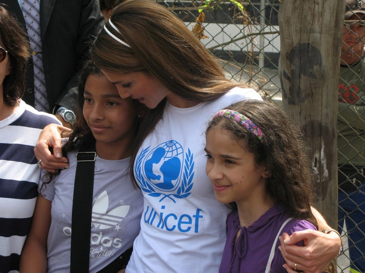 Her Majesty Queen Rania Al-Abdullah of Jordan stands arm-in-arm with two girls at the UNICEF-supported NGO Aprendiz City-School in Vila Madalena District in the city of São Paulo, Brazil.    The NGO promotes quality public education through an innovative 'learn by doing' programme. Created in 1997, it encourages children's individuality and stimulates learning in a community-supported environment.  © UNICEF/Kent Page  http://www.unicef.org