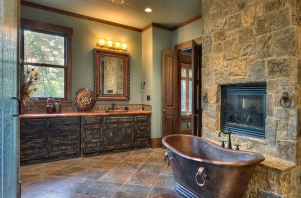 A cozy lodge bathroom featuring a stone wall with fireplace and an elegant copper tub