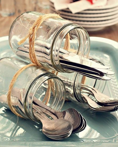 Vidros amarrados com ráfia acomodam talheres num serviço à americana