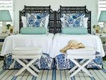 Outfitted with twin beds, lamps, side tables, and folding benches, this guest bedroom uses traditional blues and whites to create a soothing coastal space. Blue white and aqua