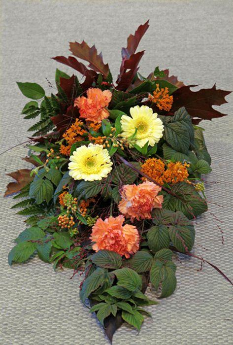 Sorgbukett. Gul germini, orange nejlika och asclepias, röda höstlöv och grönt. Nr 8B