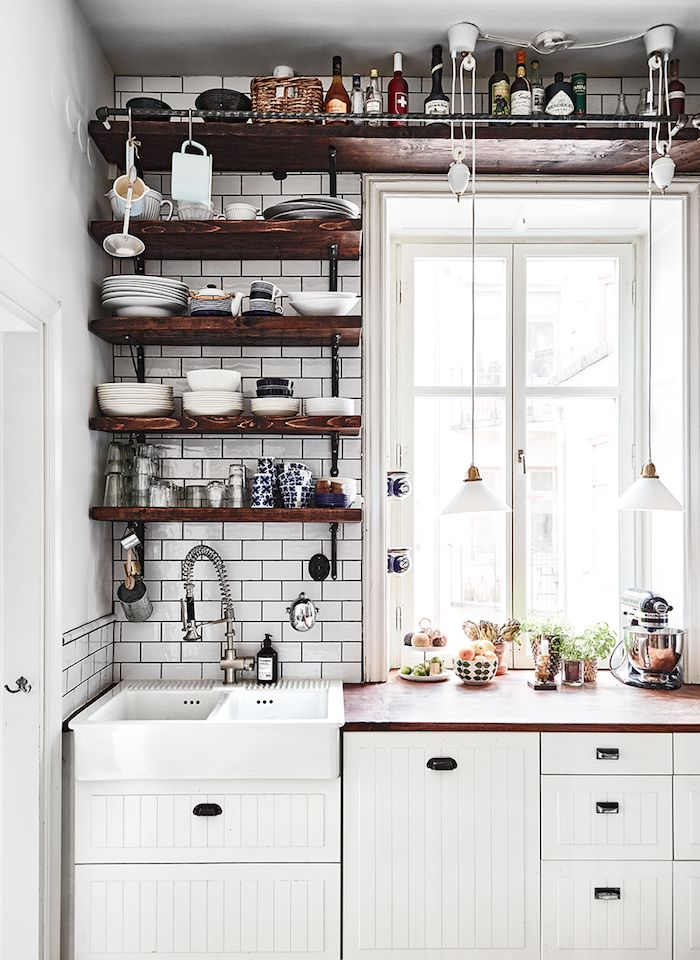 Kitchen interior with white pendant lights, dark shelving, white brick walls and white panel cabinets.