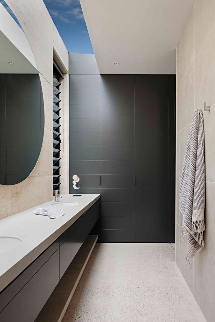 This modern ensuite features a skylight and louver windows that provide natural light, while the large round mirror helps to reflect the light throughout the space.