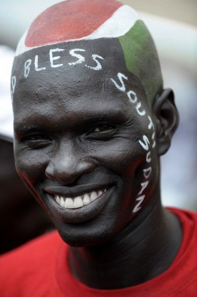 Wuor Luk, 28, a Southern Sudanese man who adorned his shaved head with the colors of the Southern Sudan flag and a 'God Bless Southern Sudan' scripture on his face smiles during a ceremony celebrating the independence of South Sudan from Sudan in the capital Juba on July 09, 2011. South Sudan separated from Sudan to become the world's newest nation.