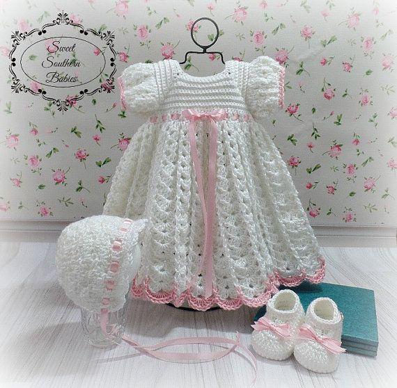 Chaque petite fille a besoin d'une robe blanche dans sa garde-robe. Fabriqué avec un fil doux bébé léger et garni d'un ruban de satin rose réglable à la taille et aux manches. Cet ensemble comprend la robe avec des chaussures Mary Jane d'assortie et un bonnet assorti.  Mary Jane chaussures sont faits uniquement pour s'adapter à jusquà 5» pieds ***  3 mois : poitrine 18 cm, épaule à lourlet 15 » 6 mois : poitrine 18,5 cm, épaule à lourlet 15,5 » 9 mois : poitrine 19 cm, épaule à lourlet : 16…