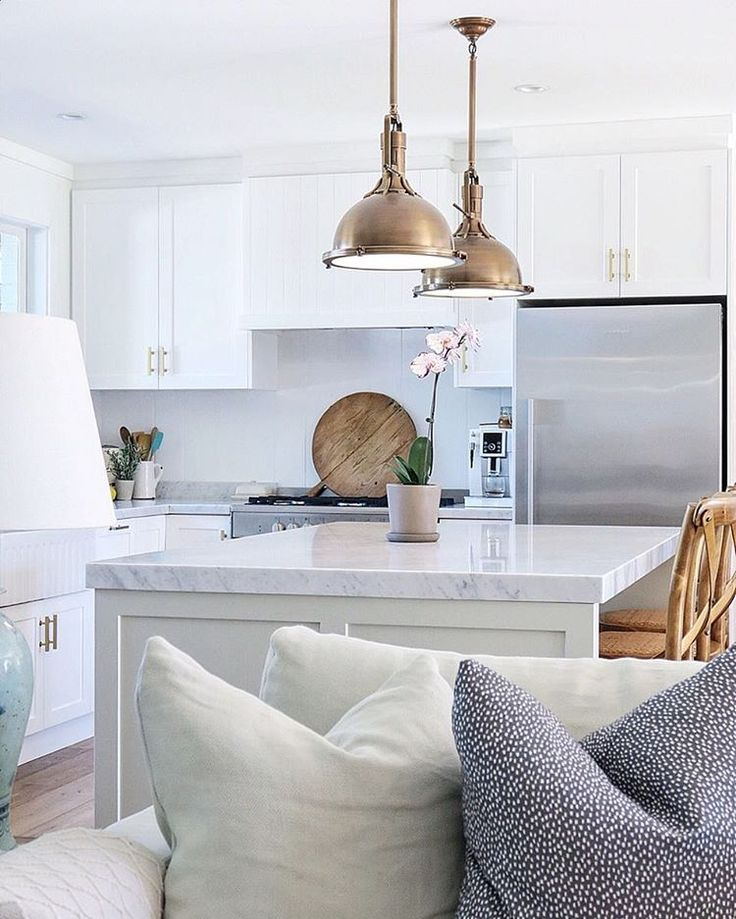 White kitchen with gold brass pendants