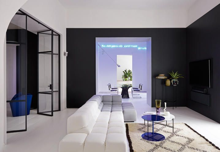 Davanti al divano di B&B Italia, design Patricia Urquiola, tappeto berbero in lana, tavolini di Cappellini in blu e di GamFratesi per Gubi. Sulla parete scura risaltano vecchi vasi da giardino. Sul fondo, il pranzo e poi l'ingresso