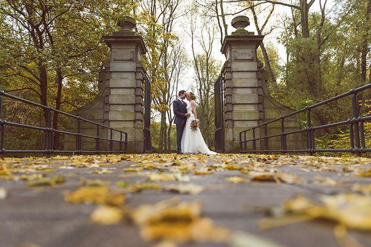 Wedding couple on bridge on wet autumn November day