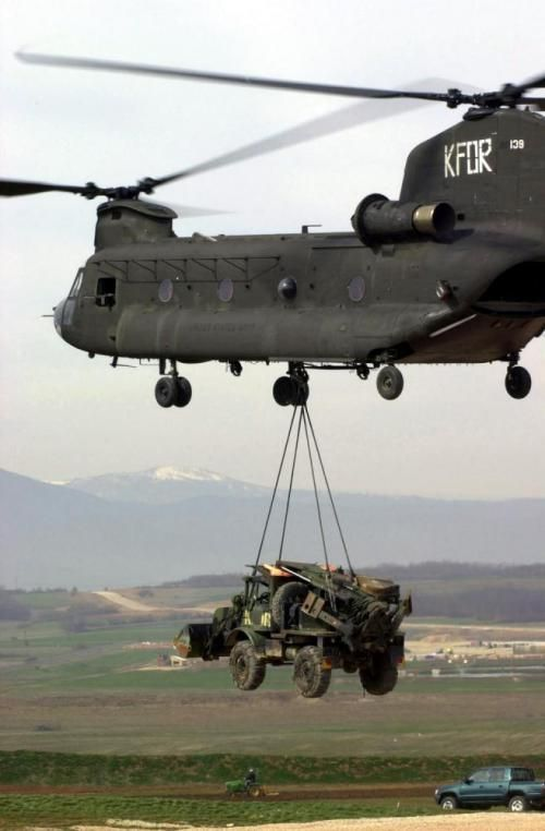 A US Army (USA) 501st Aviation Battalion CH-47 Chinook cargo helicopter carries a sling loaded USA Charlie Company (C Co), 40th Engineer (ENG) Battalion (BN), Small Emplacement Excavator (SEE) to where it will be used to build a hilltop security outpost