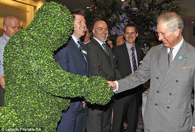 Prince Charles shakes hands with the 'living topiary statue' at the Ideal Home Show in Earl's Court
