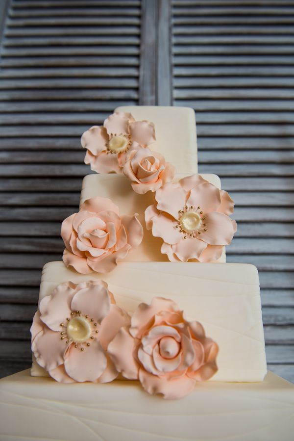 Peach blooms adorn this tiered square wedding cake.
