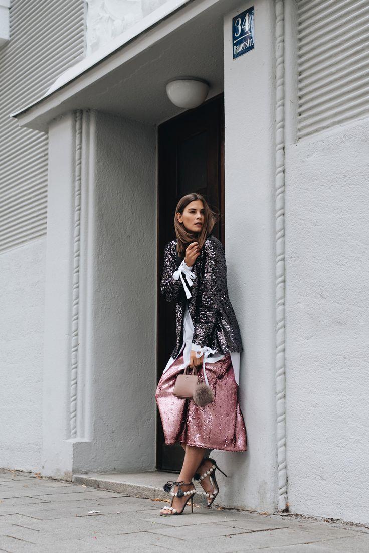 Nina Schwichtenberg trägt einen Pailletten all over Look aus schwarzem Blazer und rosa Rock, dazu eine weiße lange Bluse, eine Aigner Mini Tasche und Perlensandalen von Paula Cardemartori. Mehr auf www.fashiioncarpet.com