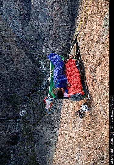 A man and woman sleep on portaledge while rock climbing a ...