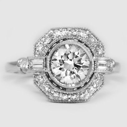 In this vintage-inspired engagement ring, a bezel-set center diamond floats above a halo of diamond accents bordered by an octagonal frame.