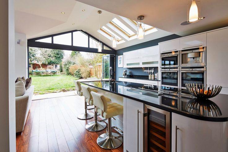 Open plan kitchen looking into a garden through open folding doors
