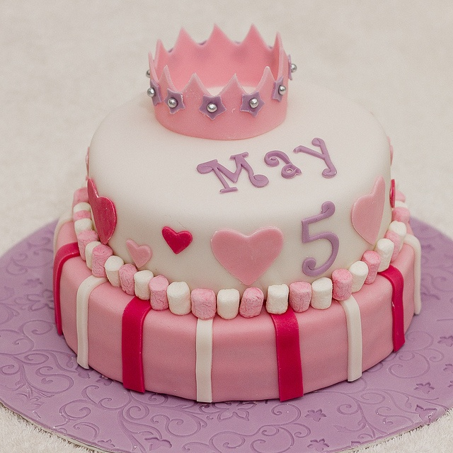 A two-tier princess crown cake decorated with hearts and flowers and trimmed with marshmallows for May
