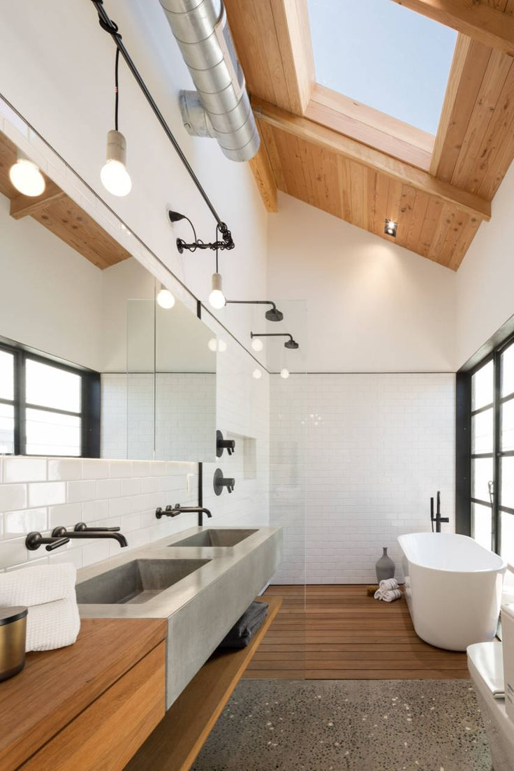 high ceiling master bathroom with skylight, black window frames, polished aggregate flooring mixed with slatted timber, SlabHaus sinks, and a long mirror for depth.