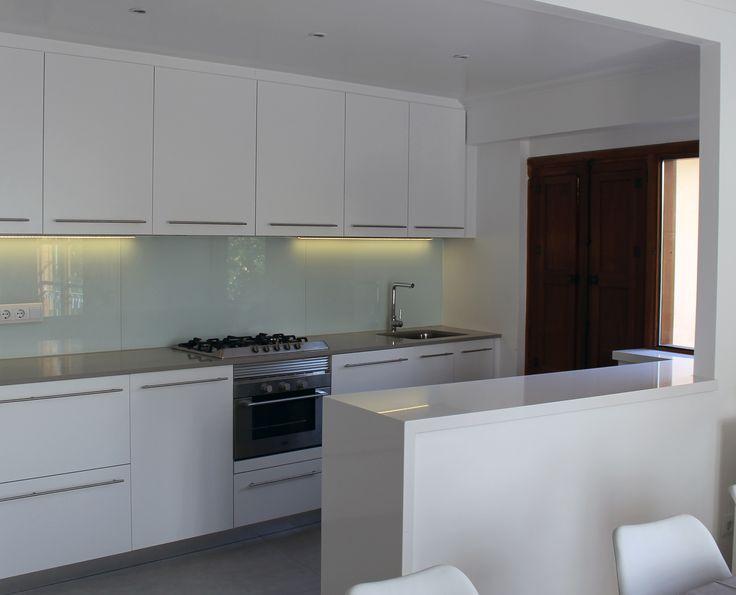 Cuina lineal amb península de Silestone Blanc Zeus separant els dos ambients de cuina i menjador.
