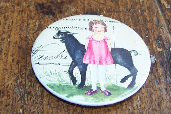 Button with girl & goat design, with magnet at back  +-5.5cm
