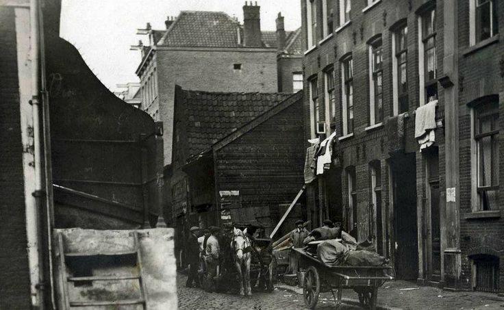 1916 Joden houttuinen  Een groepje mannen staat bij een kar met paard in de Joden Houttuinen. Beddengoed hangt over de vensterbanken van de armoedige huizen. Amsterdam