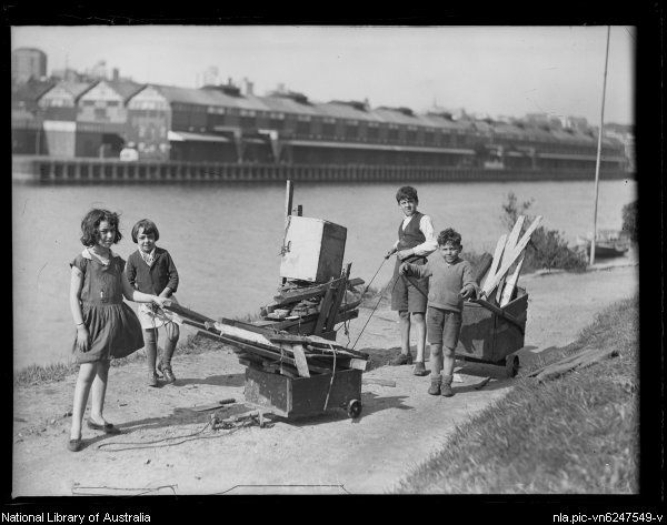 Children with billycarts filled with firewood at the Woolloomooloo wharf during the Great Depression, Sydney, 1 September 1932