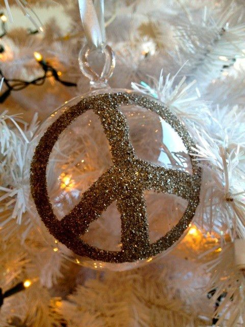 """Add some sparkle to your Christmas tree with the clear glass ornament featuring a silver sparkle peace sign. It's simple and chic! Dimensions: 5"""" diameter"""