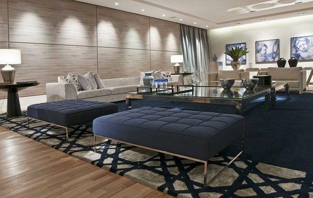 Sala com chaise e tapete azul. Parede com iluminação e porcelanto trabalhado. Living abajur