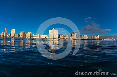 Durban Beachfront on a summers morning captured from water level in the ocean surf with a wide angle lens in a water housing.The photo image captures from the South beach Garden Court Hotel along the beachfront with the piers to the Soccer football Stadium.Durban known as Surf City and a holiday destination worldwide.