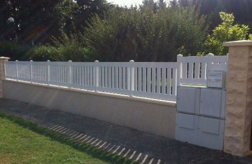 Clôture PVC à lames verticales fixée sur muret beton