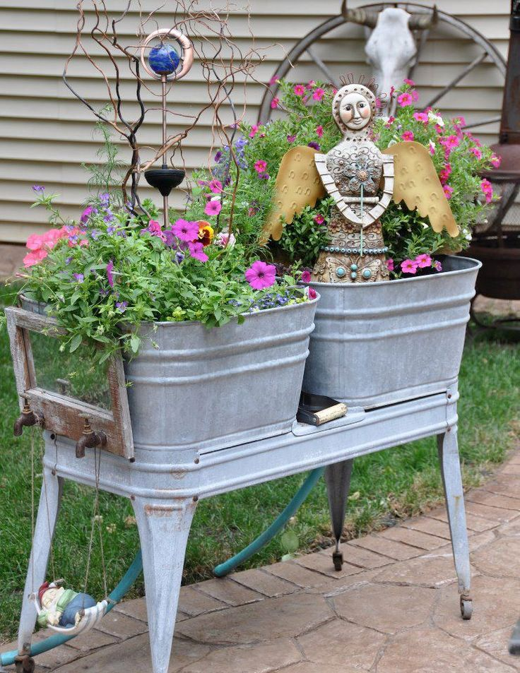 Old metal wash tubs re-purposed as planter for flowers and a garden angel.