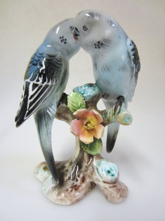 One vintage Ucagco Japan porcelain double Parakeet figure. Nice vintage condition. I can feel a tiny rough spot under one tail, but I cannot see it. A beautiful collectible! The bottom is marked PARAKEET. This was also a Souvenir as the sticker is still half on. Measurements 6 Tall x 4 Wide. Shipping $ 5.95