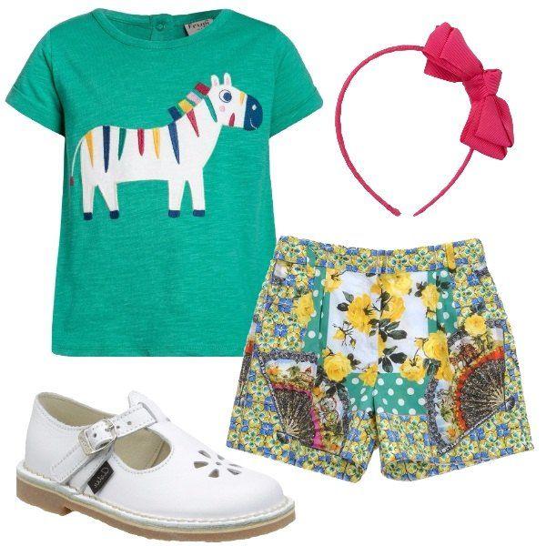 I pantaloncini Dolce & Gabbana a fantasia di fiori e ventagli colorati tipico del marchio si abbinano alla t-shirt verde con decoro sul davanti di un pony bianco con dettagli colorati. AI piedi scarpette bianche in pelle con occhielli e per finire frontino in tessuto rosso con fiocco.