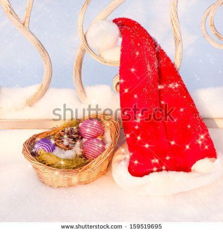 Santa Hat with Christmas basket on snow by Kamparin, via ShutterStock
