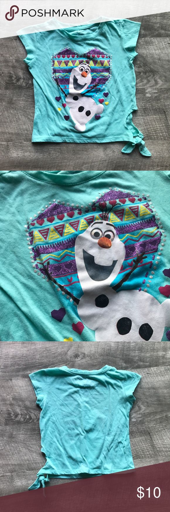 Olaf Shirt with Side Tie and Glitter Details! This shirt is so cute! I got it for our Disney World trip and then my step-daughter didn't even wear it. She ended up wearing once at home for a couple of hours. Will come freshly steamed. Glitter Details with cute printed heart. Side tie at bottom. Pairs great with purple scallop hem shorts in my closet. Bundle for a personal discount. No trades. Disney Shirts & Tops Tees - Short Sleeve
