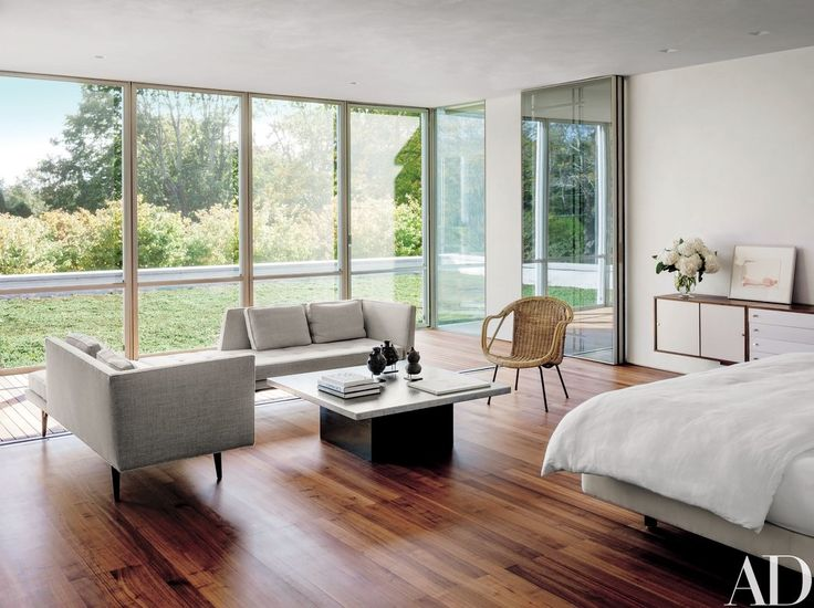Folding glass doors open the master bedroom to a porch; the midcentury Dunbar sofas are clad in a Rubelli fabric, and the cocktail table and wicker chair are vintage | archdigest.com