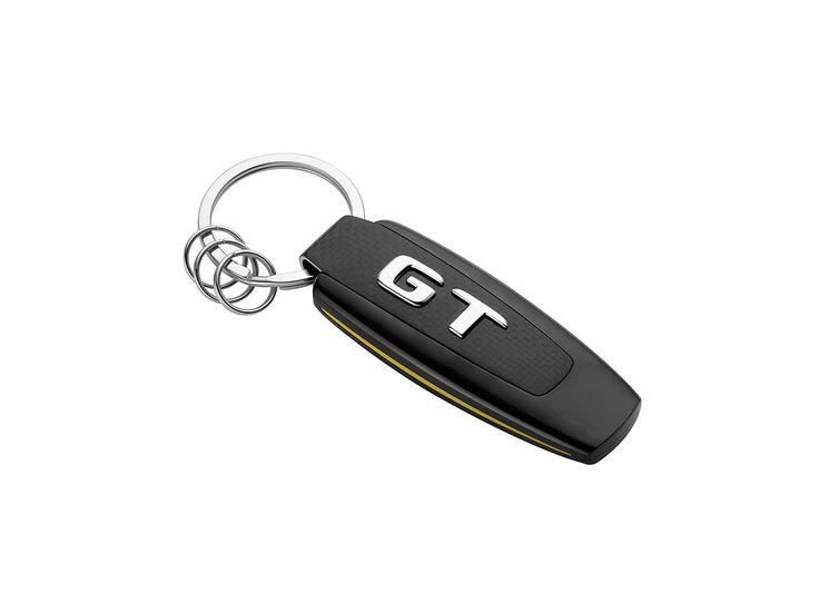 Přívěšek - klíčenka AMG GT. Stříbrná -černá - žlutá. Nerezová ocel -carbon. Plochý dělený kroužek s třemi dalšími mini-dělenými kroužky pro rychlou výměnu -odstranění jednotlivých klíčů. Logo AMG na přední straně. Navrženo v Německu. Délka cca 9 cm.