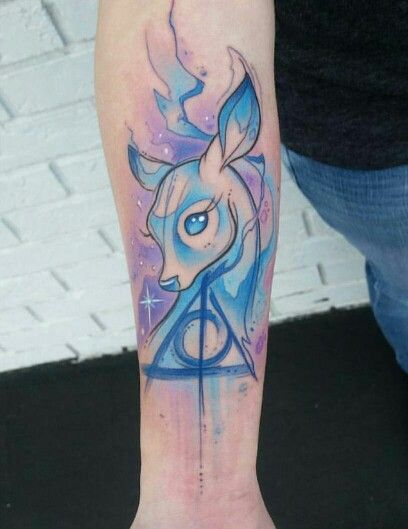Jaw dropping Patronus and Deathly Hallows watercolor tattoo.