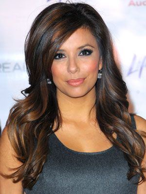 Eva Longoria's curvy hairstyle is rounded on top with big waves running throughout.