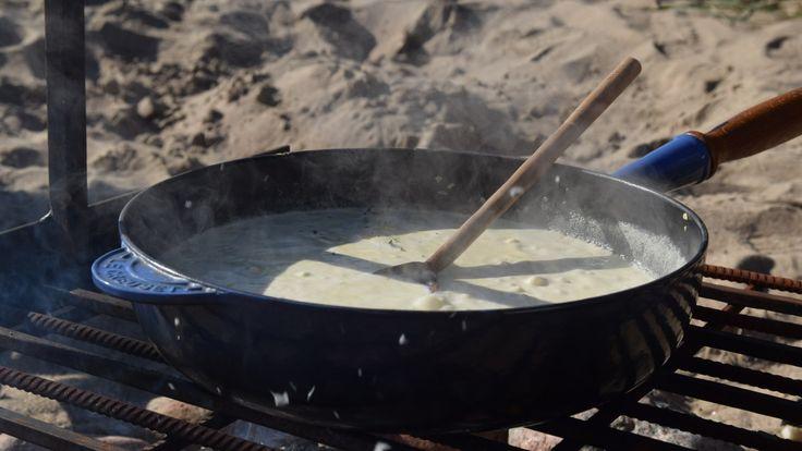 Senapssås i stekpanna på grillgaller på sandstranden.