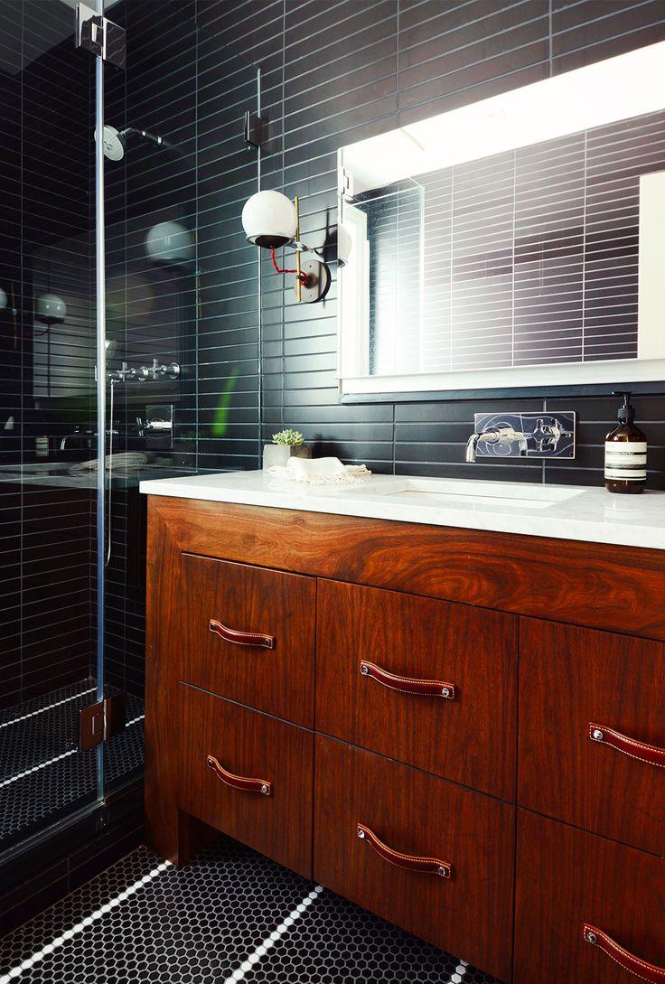 Black subway tiles in bathroom with dark wood and marble sink