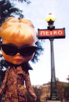 Garan often travels with a supply of Blythe dolls. For this shot taken in Paris, she positioned the doll in front of a Metro sign