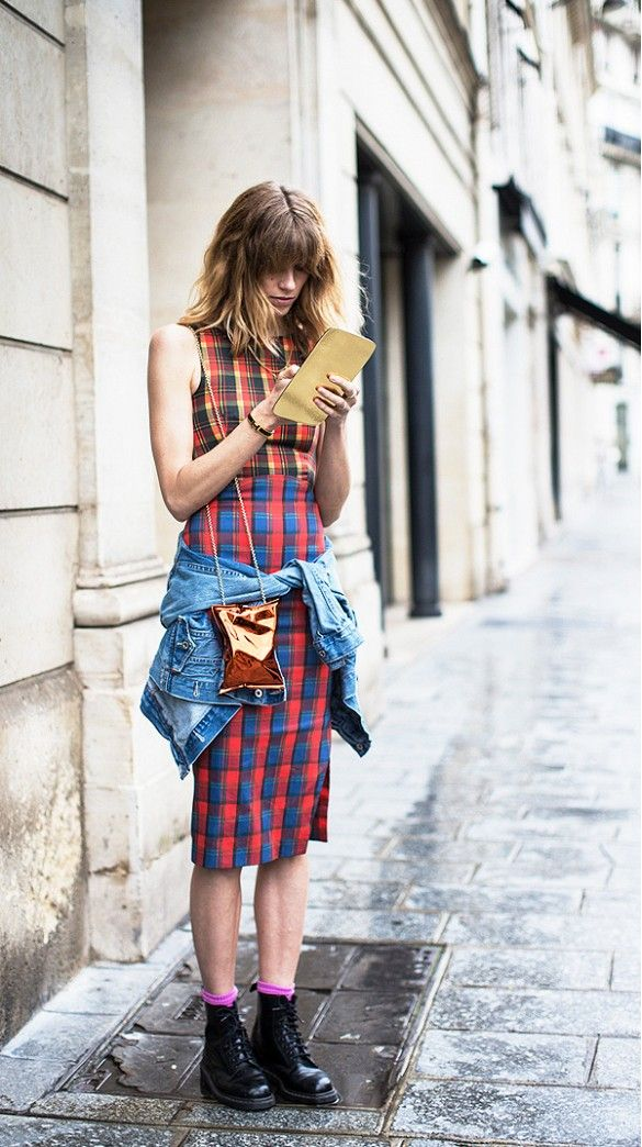 Veronika Heilbrunner wears a plaid shift dress with a denim jacket tied around the waist, Dr. Martens boots, and a metallic crossbody bag