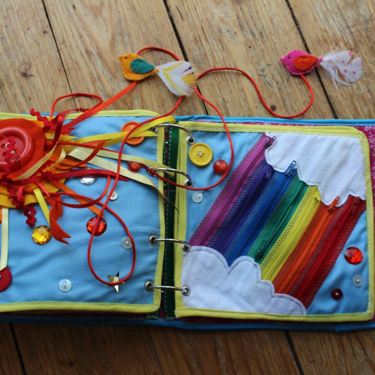 Quiet Book mamá extraterrestre libro actividades tela texturas bebé toddler arcoiris cielo cremalleras pajaros plumas botones