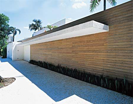 Portão de alumínio branco e muro de alvenaria com madeira cumaru (impermeabilizadas com verniz de poliuretano). Projeto Márcio Kogan