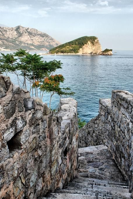 The Island of St. Nikola from the Old Town of Budva, Montenegro in the Former YUGOSLAVIA .....The City walls going down to the beach on a bright sunny day ...