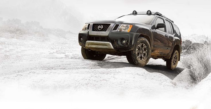 2015 Nissan Xterra in Super Black with mud on a rock
