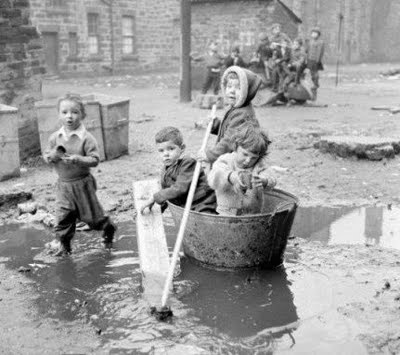 Old photograph of children in the Gorbals, Glasgow, Scotland. Housing slums in the Gorbals district of Glasgow where children use any materials to hand, an old bath tub for a boat and a few sticks for oars to play the games