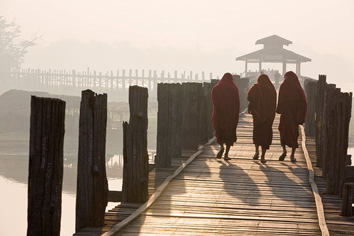 Credit: Hans Kemp/Hans Kemp Monks walk across the U Bein Bridge in Amarapura, the world's longest teakwood bridge, built in the mid 19th century. Most visitors come to the bridge to watch the sunset but early mornings offer perhaps a better opportunity to capture this unique structure.