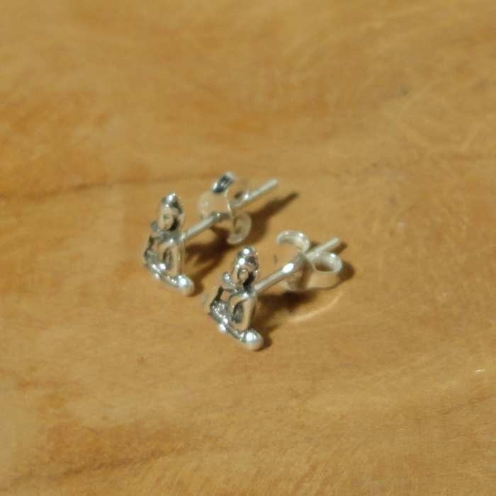 Fair Trade sterling silver stud earrings from Thailand in the shape of Buddha. The length of the studs is 1.5 cm and the Buddha is 0.9 cm x 0.6 cm x 0.1 cm.    A part of the profits of these jewelry is donated to the Tibetan Children's Education Foundation, an organisation who takes care of the well-being and the education of Tibetan children in exile.